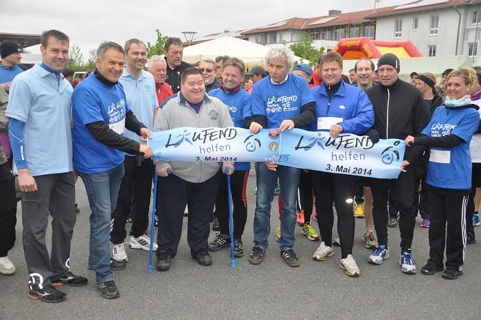 Gruppe von Läufern hält Banner vom Benefizlauf